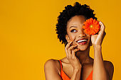 Portrait of a happy excited young woman holding orange gerbera daisy covering her eye and looking up at copy space