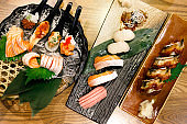 set of sushi and rolls with salmon, tuna, scallop and unagi on stone board