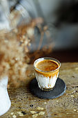 Glass of coffee with milk on rustic wooden table.