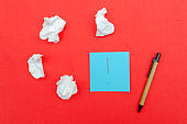 Blue sheet of paper with an exclamation mark, crumpled paper and pen on a red background, top view.