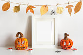 Halloween ceramic pumpkins, floral garland and frame on table wall background. Greeting card template