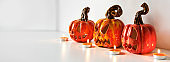 Halloween ceramic pumpkins jack lantern and candles on table wall background. Home decoration, banner format
