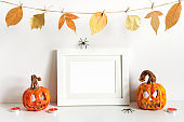 Halloween composition with ceramic pumpkins, floral garland and frame on table wall background. Greeting card template
