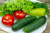 beautiful fresh, juicy vegetables on a white plate: fresh peppers, tomatoes, cucumbers, lettuce, dill