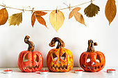 Ceramic Jack Lanterns and autumn leaves garland on table wall background. Home decoration