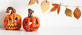 Banner with Ceramic Jack Lanterns and autumn leaves garland on table wall background