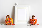Halloween composition with ceramic pumpkins jack lantern and frame on table wall background. Greeting card template
