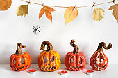 Halloween composition with ceramic pumpkins jack lantern and candles on table wall background. Home decoration