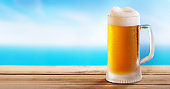 cold mug of beer on a wooden table on background of the sea