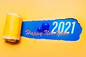 Happy new year, new start, new page of life; resolution concept. Text of 2021 on blue background in hole of torn yellow paper.