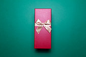 Close-up of red gift box with golden bow on background of green color.