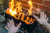 kids warming their arms over fire and grill on red brick wall background in backyard
