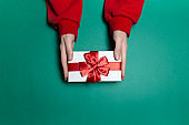 Top view of female hands holding white gift box with red bow on background of green color.