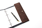 Leather-bound business notebook with a Parker pen on a white background. Business concept