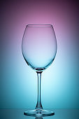 The wine glass is empty with purple and blue color filters. Photo of glass on the lumen with filters. Vertical photo