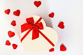 Box. Heart-shaped gift box with red ribbon stands in the middle on a white background with little red cardboard hearts. The view from the top. Valentine's day and Birthday
