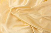 Smooth elegant golden silk or satin luxury cloth texture can use as wedding background. Luxurious background design.  Retro style
