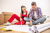 Young couple in casual clothes and an overall plan the apartment decoration over paper plans.