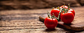 Bunch of fresh tomatoes on a rustic wooden surface