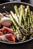 Asparagus eggs bacon and garlic in ceramic pan