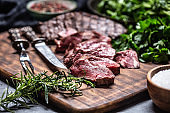 Slices of juicy grilled beef steak with fork and knife on a butcher plate
