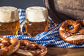 Oktoberfest two beer with pretzel wooden barrel and blue tablecloth