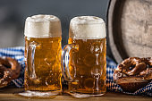 Oktoberfest two large beer with pretzel wooden barrel and blue tablecloth