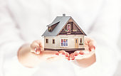 Hands of young woman holding model house, real estate insurance and banking concept