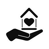 House with heart in hand black color vector icon isolated on white background.