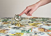little globe on the table with money. female hand indicates a place on the map. concept on the topic of finance and travel