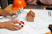 Hand holding banknote and house model. Real estate concept. Home construction financing.