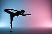 Young fit woman practicing yoga. Neon lights.