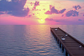 Wooden bridge pier on the sea with spheres, sunset
