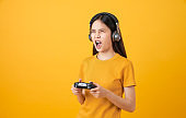Cheerful beautiful Asian woman in casual yellow t-shirt and playing video games using joysticks with headphones on orange background.