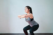 Smiley Asian woman wearing sportswear and practice yoga in living room. Healthy lifestyle concept.