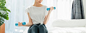 Asian woman sitting on the bed and doing exercises with small blue dumbbells, Warm-up the body in the morning. wellness concept.