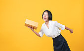 Young smiling asian woman hands showing cardboard boxes on light orange background.