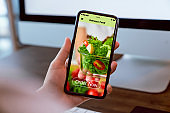 Woman using smartphone and touching application screen for ordering salad online on the table at office.