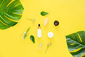 White bottle cream, mockup of beauty product brand. Top view on the yellow background.