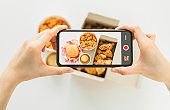 Hand using smartphone with fast food fried chicken photography.