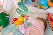 A two-month-old baby looks at the crib toys. Development of motor skills and vision in a newborn