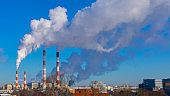 Panoramic industrial landscape, pipes emitting thick smoke into the atmosphere, air pollution with toxic substances, environmental problems