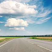 asphalt road to horizon and blue sky with clouds over it