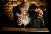 Close-up. Young girl bartender carefully decorates glass of rose drink and sprinkles on it