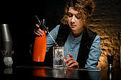 Young female bartender attentively pours carbonated drink to glass using siphons.