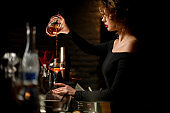 Sexy woman bartender in dark bar masterfully pours cocktail into wineglass.