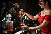 attractive young girl in red blouse pours alcoholic drink into glass at bar.