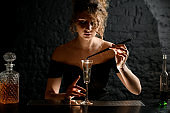 female bartender holds tweezers with plant over glass