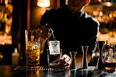 Bartender putting precisely ice cube in cocktail glass