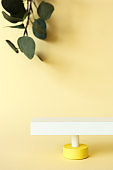 Abstract pedestal on pastel yellow background with copy space and defocused eucalyptus leaves, front view. Minimalist scene with podium for promotion, cosmetic product show, vertical